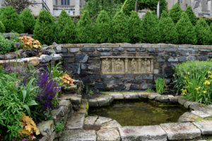 fountain with flowers and stone carvings at the Bishop's Garden, Washington National Cathedral in Washington, DC