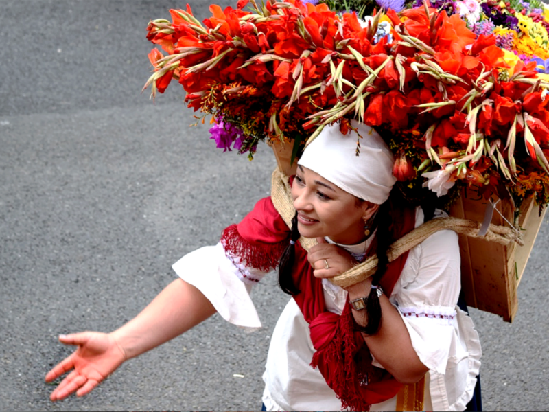 farmers carry silletas (large floral displays) in The Desfile de Silleteros (Parade of Flowers) during the Feria de las Flores is an annual festival in Colombia, South America